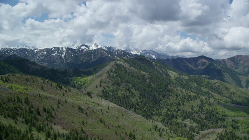 6K stock footage aerial video of passing green mountains with snowy peaks in the distance, Wasatch Range, Utah Aerial Stock Footage | AX140_230