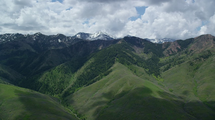 Flying by green mountains, snowy peaks in the distance, Wasatch Range, Utah Aerial Stock Footage | AX140_235