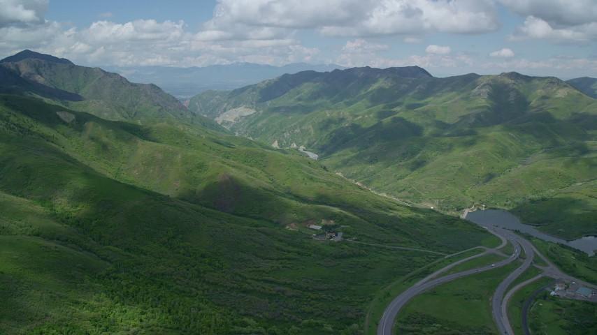 Approaching Interstate 80 through mountains, Wasatch Range, Utah Aerial Stock Footage   AX140_238