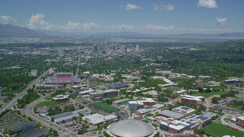 6K stock footage aerial video fly over University of Utah, Jon M. Huntsman Center to approach Downtown Salt Lake City, Utah Aerial Stock Footage | AX140_248