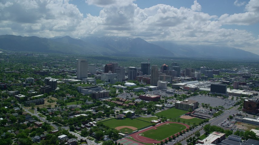 6K stock footage aerial video of flying by downtown, Wasatch Range in distance, Downtown Salt Lake City, Utah Aerial Stock Footage | AX140_258