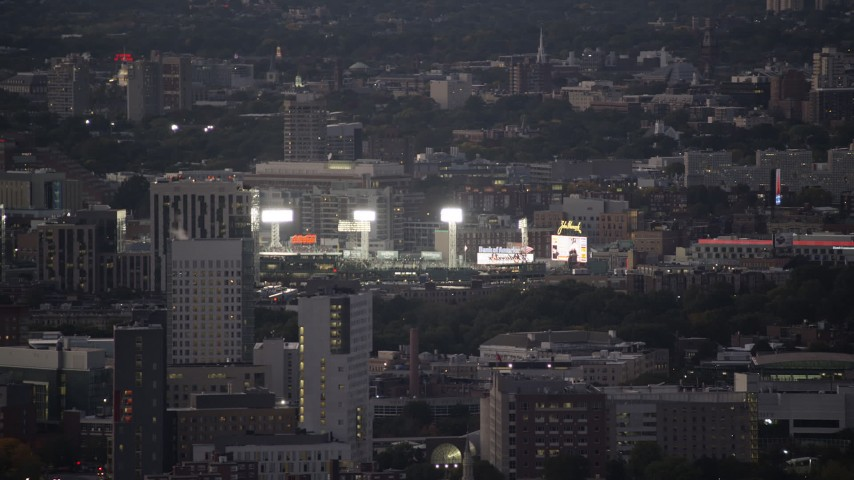 6K stock footage aerial video flying by baseball game, bright lights, Fenway Park, Boston, Massachusetts, twilight Aerial Stock Footage | AX141_013