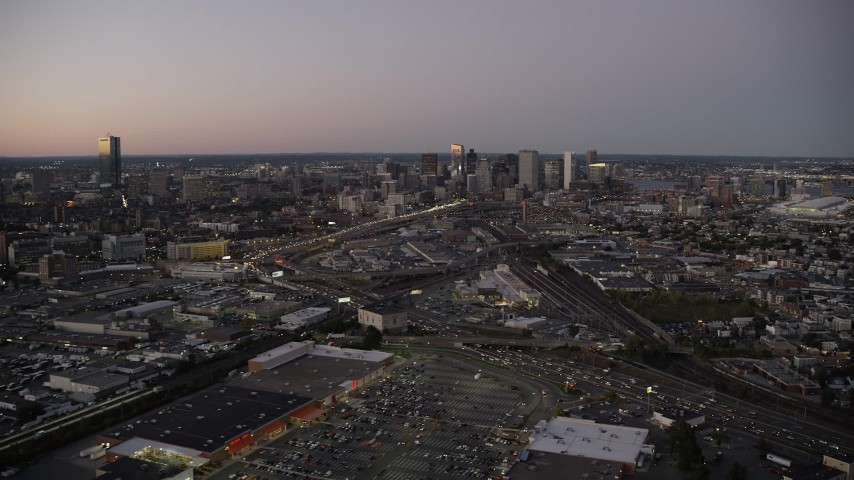 6K stock footage aerial video flying over heavy traffic, by Downtown Boston skyline, Massachusetts, twilight Aerial Stock Footage   AX141_015