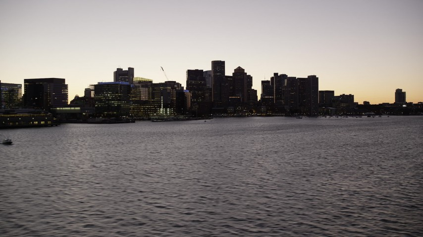 6K stock footage aerial video flying low over water, approaching skyline, Downtown Boston, Massachusetts, twilight Aerial Stock Footage   AX141_022