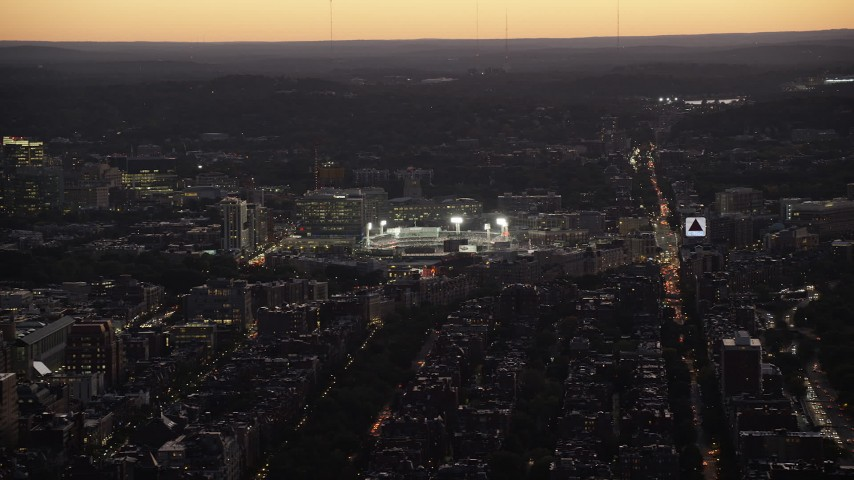 6K stock footage aerial video flying by Fenway Park under lights, Boston, Massachusetts, twilight Aerial Stock Footage | AX141_029