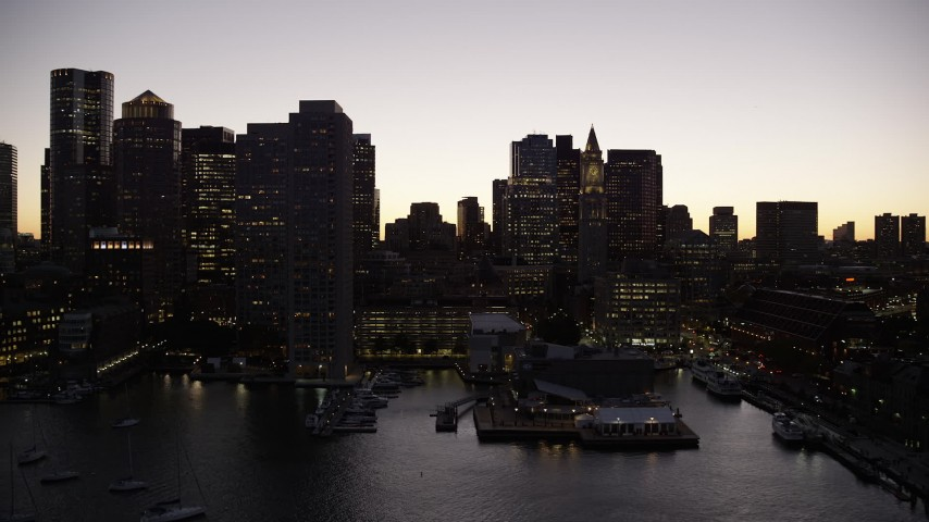 6K stock footage aerial video flying over harbor and by the skyline, Downtown Boston, Massachusetts, twilight Aerial Stock Footage | AX141_032