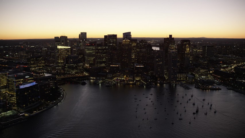 6K stock footage aerial video flying by downtown skyline from over water, Downtown Boston, Massachusetts, twilight Aerial Stock Footage | AX141_043