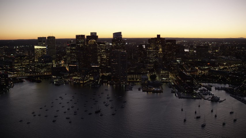 6K stock footage aerial video flying by the skyline from over the harbor, Downtown Boston, Massachusetts, twilight Aerial Stock Footage | AX141_044