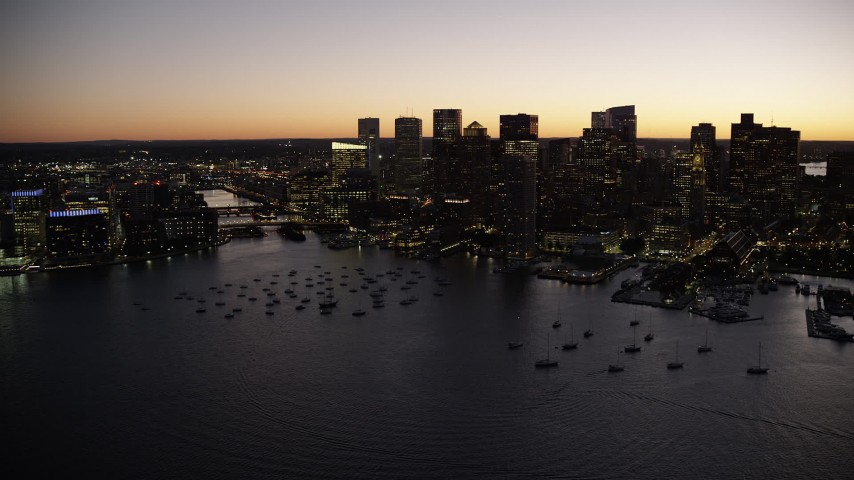 6K stock footage aerial video flying over harbor, by boats, skyline, Downtown Boston, Massachusetts, twilight Aerial Stock Footage | AX141_045