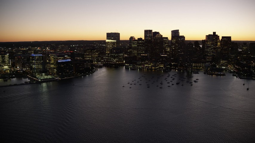 6K stock footage aerial video flying by boats in harbor, skyline, Downtown Boston, Massachusetts, twilight Aerial Stock Footage | AX141_046