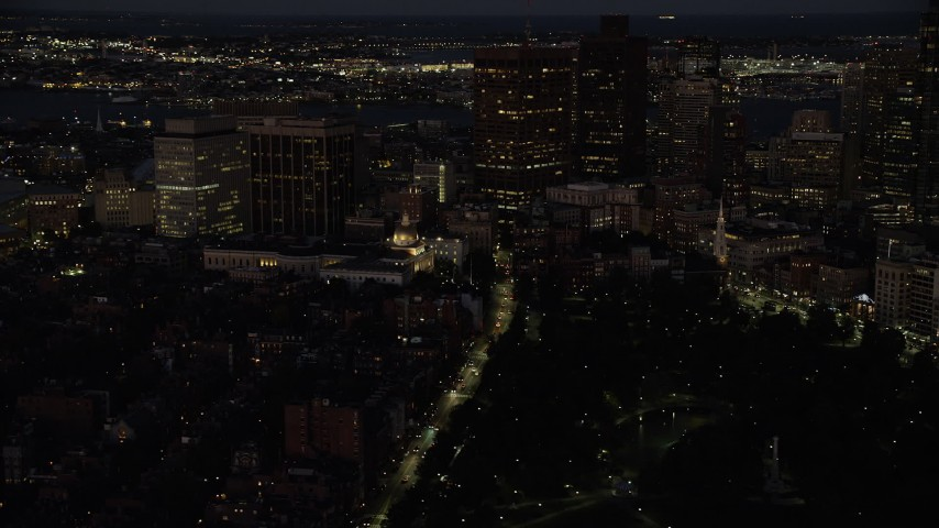 6K stock footage aerial video flying by Massachusetts State House, skyscrapers, Downtown Boston, Massachusetts, night Aerial Stock Footage | AX141_056