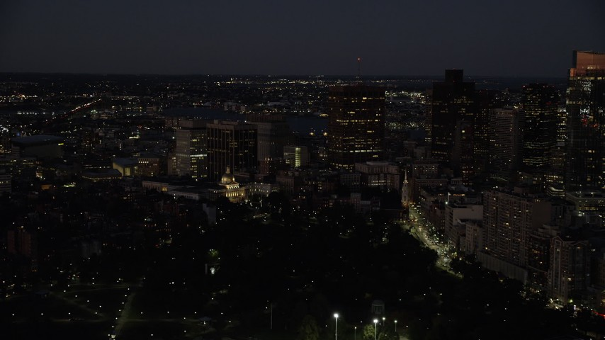 6K stock footage aerial video flying by skyscrapers, Massachusetts State House, Downtown Boston, Massachusetts, night Aerial Stock Footage | AX141_057