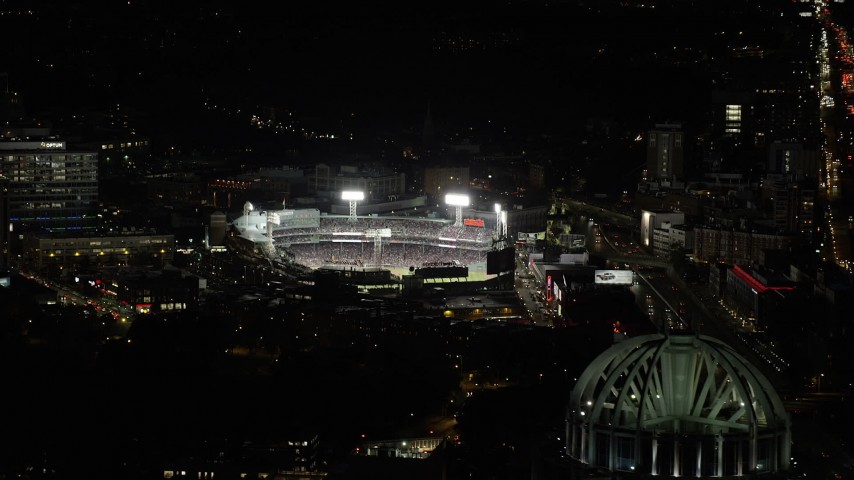 6K stock footage aerial video flying by baseball game, Fenway Park, eclipsed by Prudential Tower, Boston, Massachusetts, night Aerial Stock Footage | AX141_079