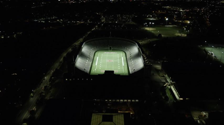 6K stock footage aerial video approaching a well-lit Harvard Stadium, tilt down, Harvard University, Massachusetts, night Aerial Stock Footage   AX141_106