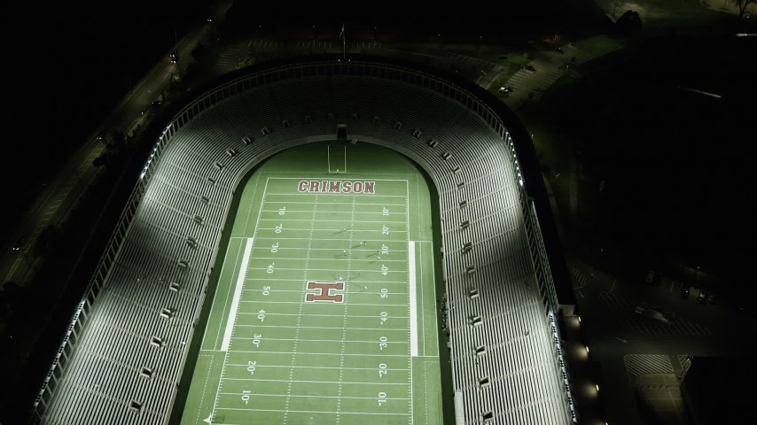 6K stock footage aerial video of a bird's eye view over a well-lit Harvard Stadium, Harvard University, Massachusetts, night Aerial Stock Footage | AX141_107
