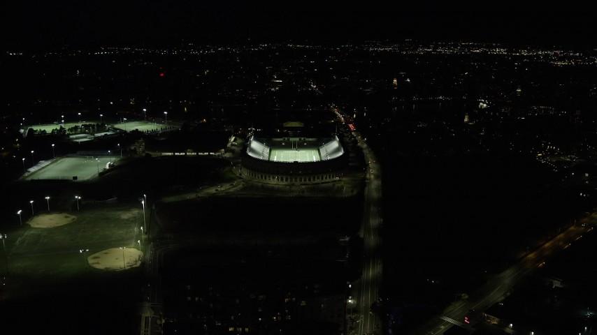 6K stock footage aerial video flying by sports fields, approaching Harvard Stadium, Harvard University, Massachusetts, night Aerial Stock Footage | AX141_109