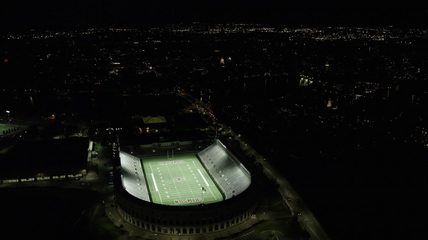 6K stock footage aerial video flying by Harvard Stadium with the lights on, Harvard University, Massachusetts, night Aerial Stock Footage | AX141_110