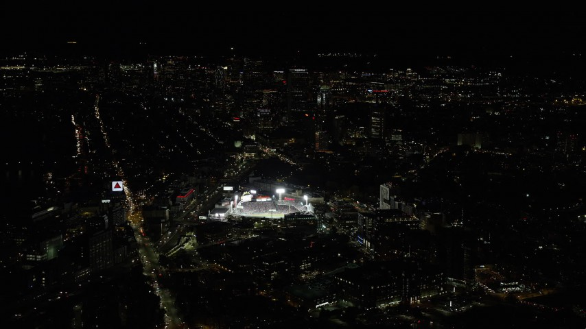 6K stock footage aerial video flying by baseball game, skyscrapers, Fenway Park, Downtown Boston, Massachusetts, night Aerial Stock Footage | AX141_130