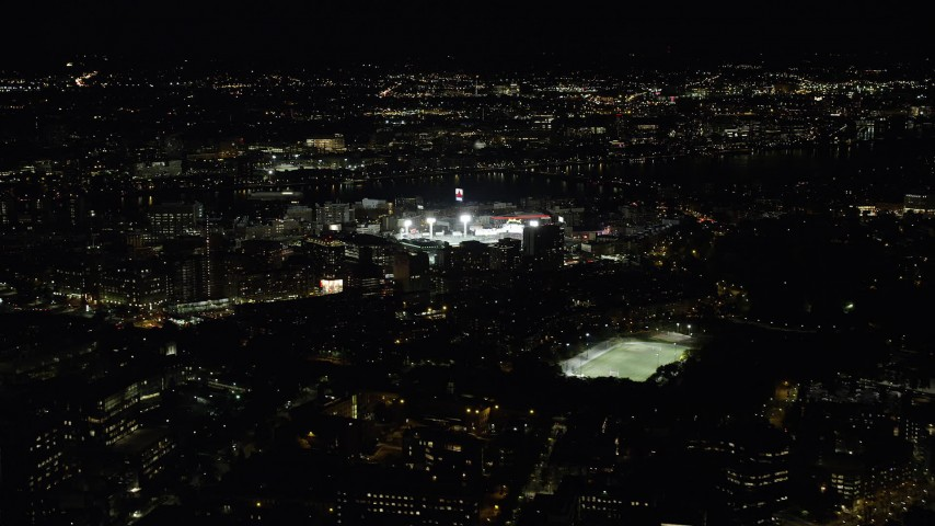 6K stock footage aerial video flying away from a baseball game, Fenway Park, Boston, Massachusetts, night Aerial Stock Footage | AX141_133
