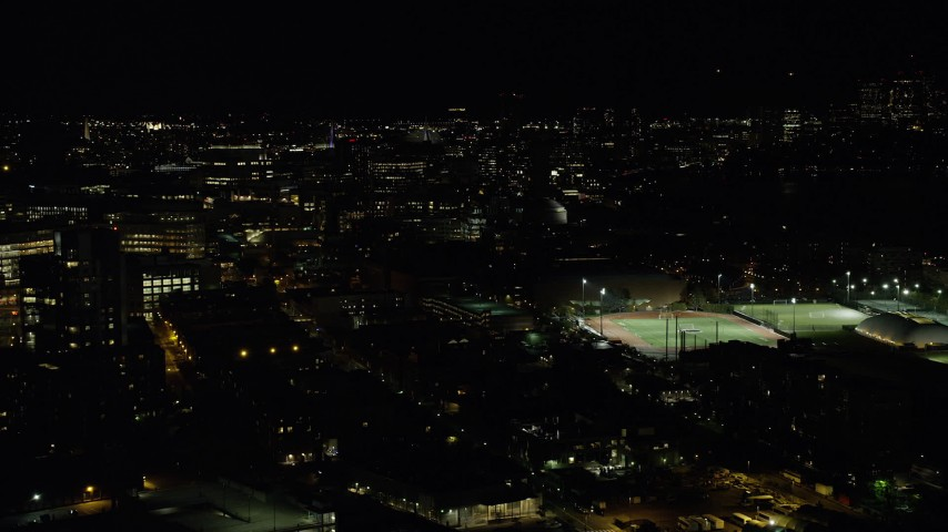 6K stock footage aerial video flying by sports fields, Massachusetts Institute of Technology, Cambridge, Massachusetts, night Aerial Stock Footage | AX141_146