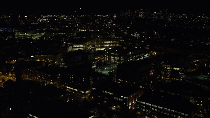 6K stock footage aerial video flying by office buildings, parking structures, Cambridge, Massachusetts, night Aerial Stock Footage   AX141_149