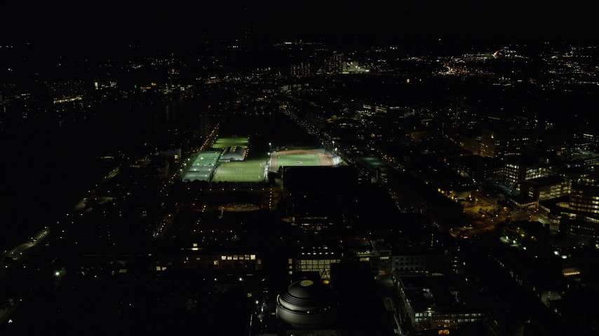 6K stock footage aerial video approaching sports fields and Massachusetts Institute of Technology, Cambridge, Massachusetts, night Aerial Stock Footage | AX141_169