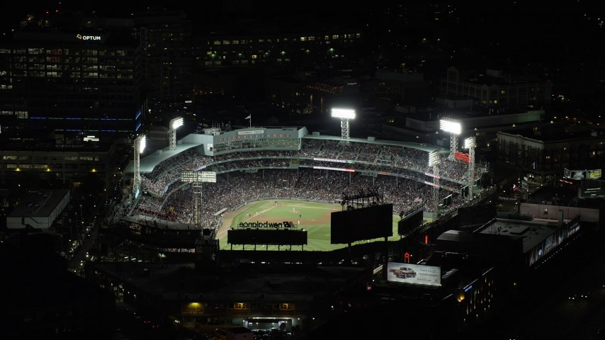 6K stock footage aerial video orbiting baseball game and busy city streets, Fenway Park, Boston, Massachusetts, night Aerial Stock Footage | AX141_187