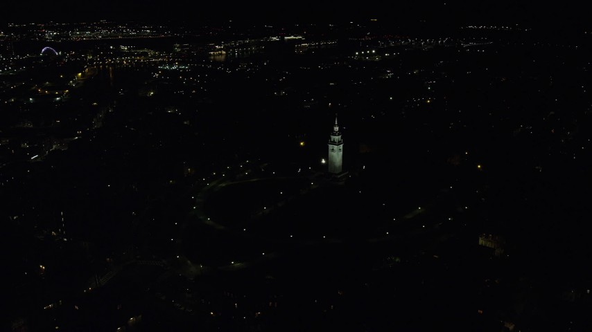 6K aerial video orbiting Dorchester Heights Monument, reveal skyline, South Boston, Downtown Boston, Massachusetts, night Aerial Stock Footage | AX141_223