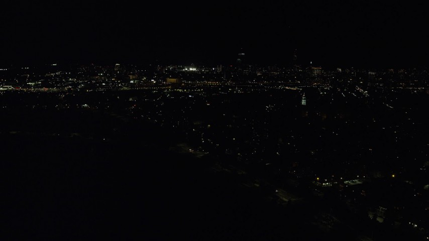 6K stock footage aerial video flying by Dorchester Heights Monument, skyline, South Boston, Downtown Boston, Massachusetts, night Aerial Stock Footage | AX141_227