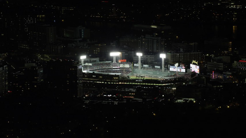 6K stock footage aerial video orbiting away from a baseball game at night at Fenway Park, Boston, Massachusetts Aerial Stock Footage | AX141_245