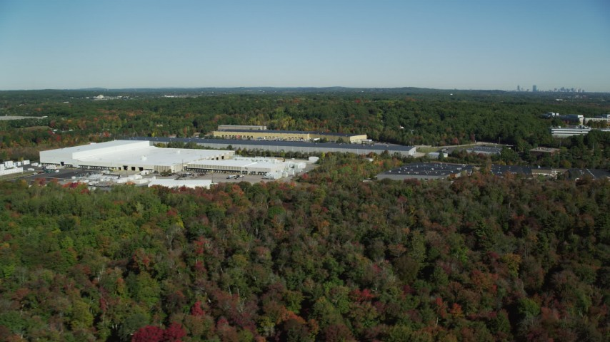 6K stock footage aerial video flying by warehouses surrounded by trees in autumn, Westwood, Massachusetts Aerial Stock Footage | AX142_001