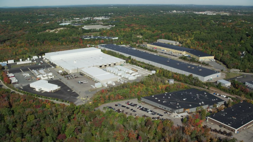 6K stock footage aerial video flying by warehouses surrounded by trees in autumn, Westwood, Massachusetts Aerial Stock Footage | AX142_002