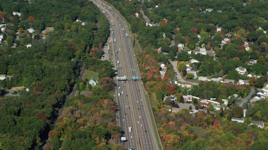 6K stock footage aerial video flying by Interstate 93, homes, trees, autumn, Westwood, Massachusetts Aerial Stock Footage | AX142_005