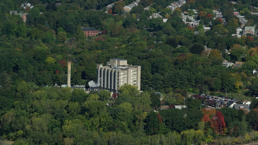6K stock footage aerial video flying by factory and smoke stack, trees in autumn, Hyde Park, Massachusetts Aerial Stock Footage | AX142_012