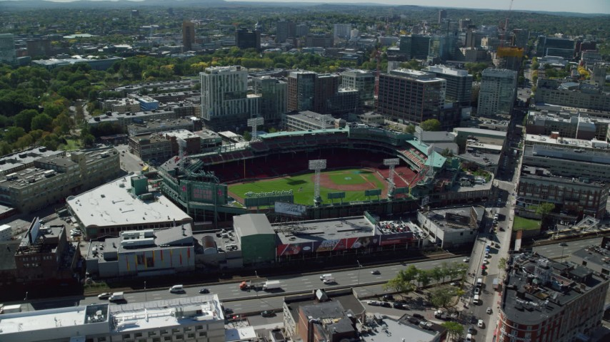 6K stock footage aerial video flying by Fenway Park on a sunny day, Boston, Massachusetts Aerial Stock Footage | AX142_162
