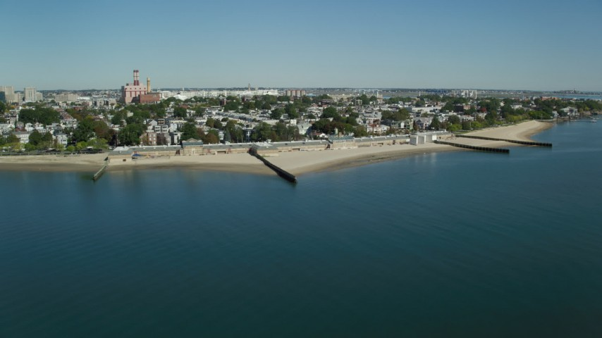 6K stock footage aerial video flying by coastal community, beach, breakwaters, South Boston, Massachusetts Aerial Stock Footage | AX142_209