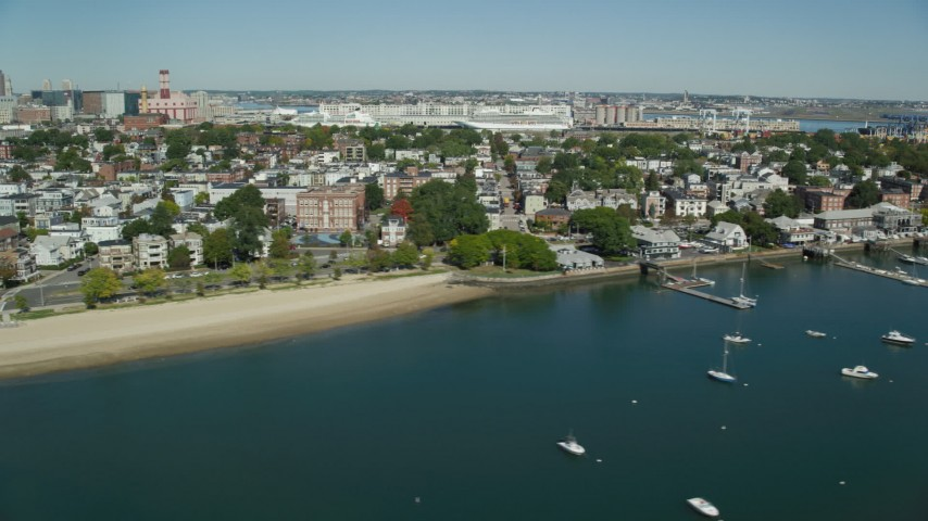 6K stock footage aerial video flying by coastal community, beach, reveal piers, boats, South Boston, Massachusetts Aerial Stock Footage | AX142_245