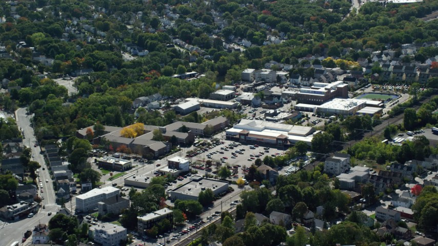 6K stock footage aerial video flying by large strip mall, neighborhoods, Hyde Park, Massachusetts Aerial Stock Footage | AX142_318