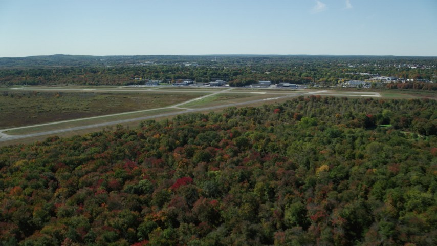 6K stock footage aerial video approaching and flying over airport in autumn, Norwood Memorial Airport, Massachusetts Aerial Stock Footage AX142_325