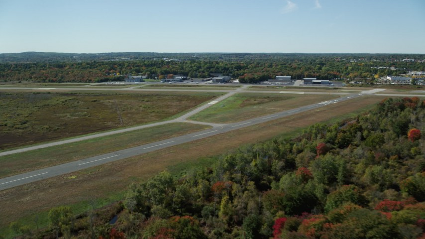 6K stock footage aerial video flying over trees in autumn, approaching Norwood Memorial Airport, Massachusetts Aerial Stock Footage | AX142_326