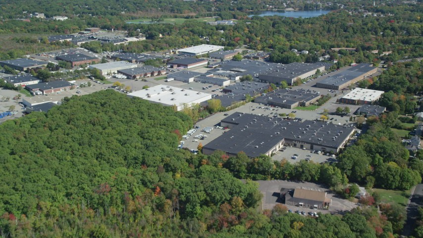 6K stock footage aerial video flying over forest, approach warehouse buildings, autumn, Braintree, Massachusetts Aerial Stock Footage | AX143_006