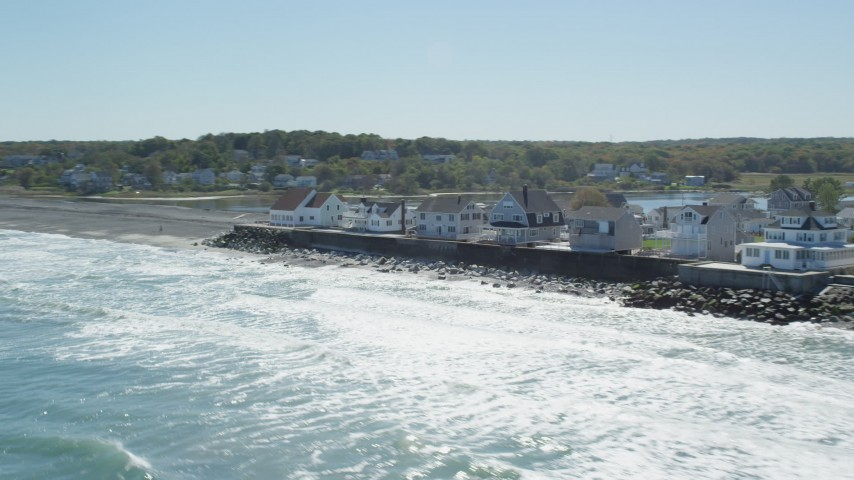 6K aerial video flying by oceanfront homes, pan right, Scituate, Massachusetts Aerial Stock Footage | AX143_033