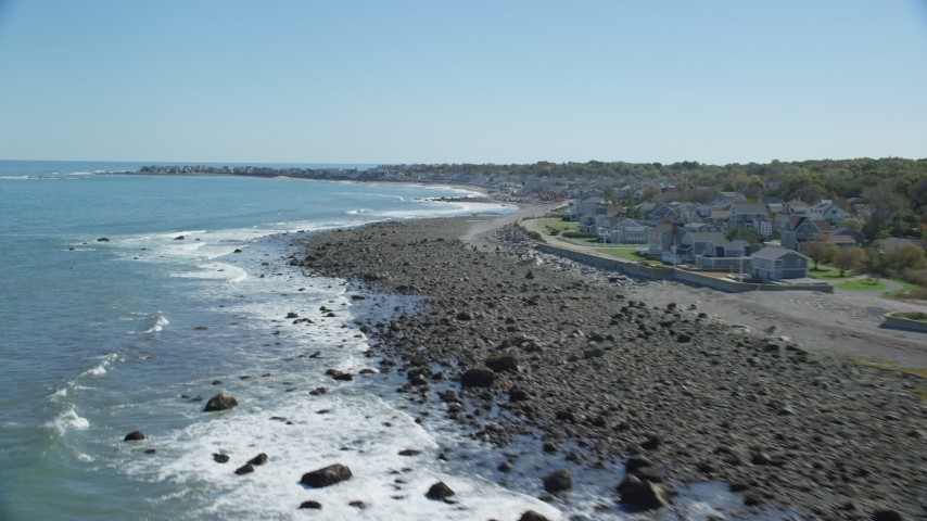 Flying by waves rolling onto beach, coastal community, Scituate, Massachusetts Aerial Stock Footage | AX143_035