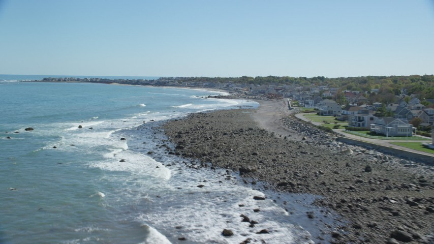 6K stock footage aerial video flying by waves rolling onto beach, coastal community, Scituate, Massachusetts Aerial Stock Footage | AX143_035