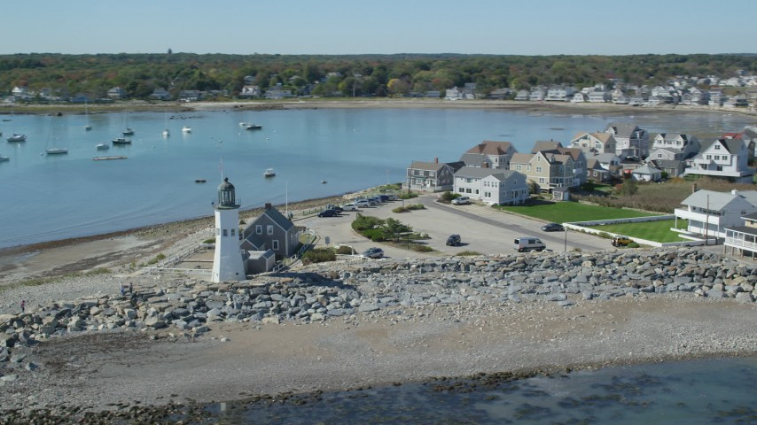 6K aerial video orbiting Old Scituate Light, beach, oceanfront homes, Scituate, Massachusetts Aerial Stock Footage AX143_040