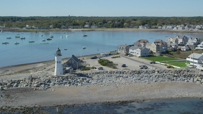 Orbiting a beach, oceanfront homes, Old Scituate Light, Scituate, Massachusetts Aerial Stock Footage | AX143_041
