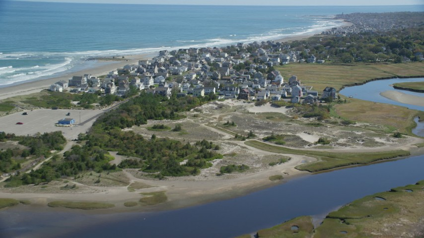 Flying by oceanfront homes, waves crashing, Marshfield, Massachusetts Aerial Stock Footage | AX143_054