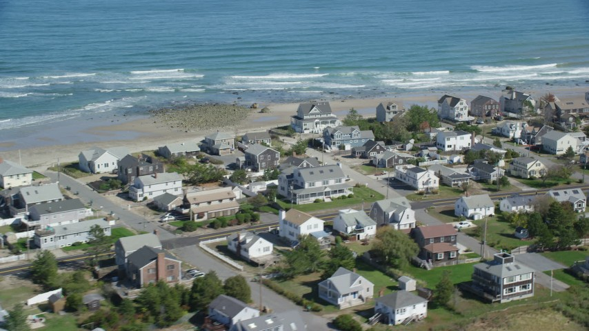 6K aerial video flying by oceanfront homes, waves crashing, Marshfield, Massachusetts Aerial Stock Footage | AX143_055