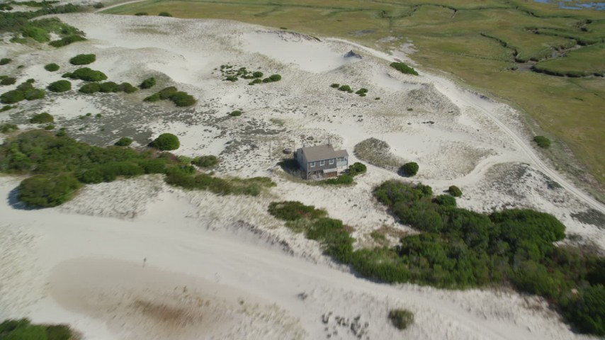6K aerial video flying over sand dunes, beach, approach isolated home, Barnstable, Massachusetts Aerial Stock Footage | AX143_135