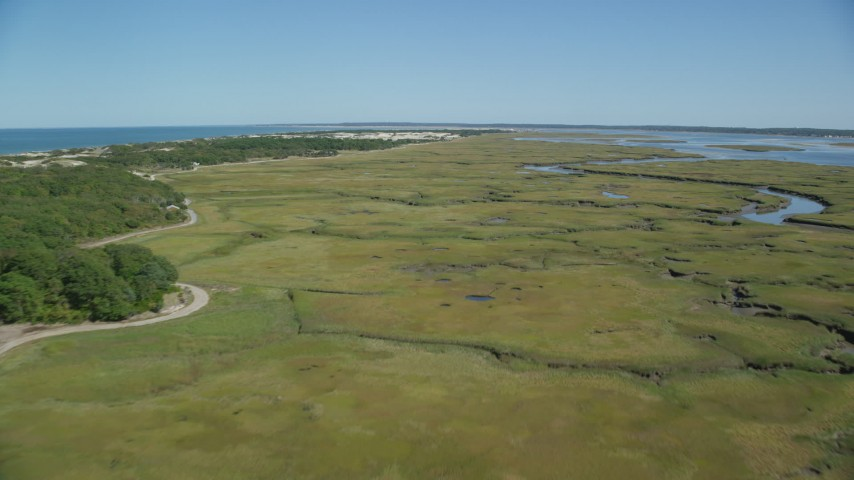 6K aerial video flying over marshland, by isolated homes, coastal road, Barnstable, Massachusetts Aerial Stock Footage | AX143_136